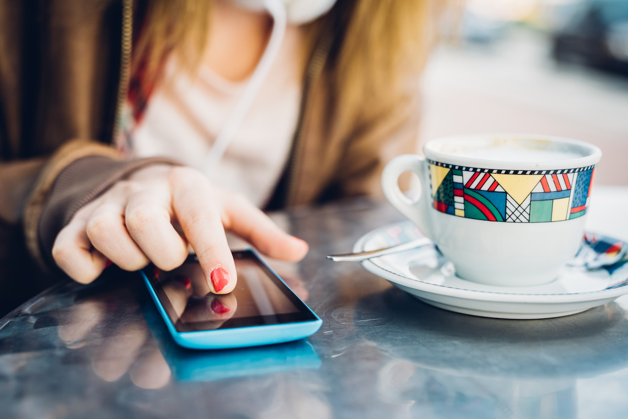 Close up on the hand of young woman tapping the screen of a smart phone, having a coffee - technology, communication, social network concept